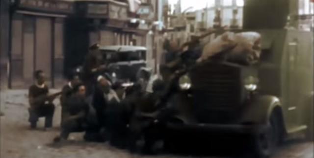 """Milicianos disparando en Zocodover tras un carro blindado modelo """"Bilbao"""" . Captura de un vídeo real a color de la Guerra Civil en Toledo en el verano de 1936"""
