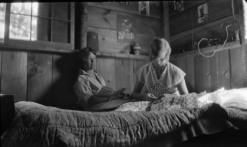 Two women inside a rustic cabin