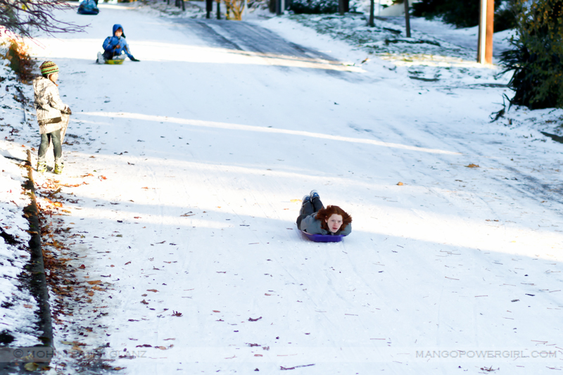 kids sledding downhill