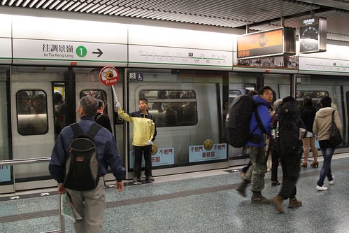 Platform attendants at Choi Hung holding up a 'stop' sign towards approaching passengers, to allow the doors to close
