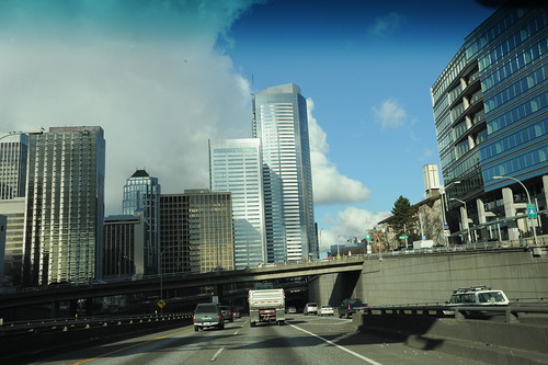 Cloud cover opens, the silver steel jet city, from Highway 5, skyscrapers, steel, concrete, Seattle, Washington, USA by Wonderlane