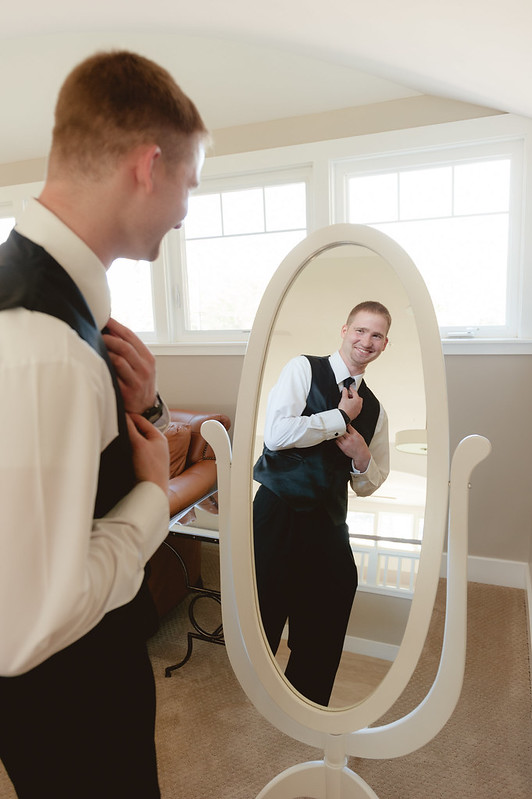 The groom jokes around and laughs while fixing his tie before his wedding