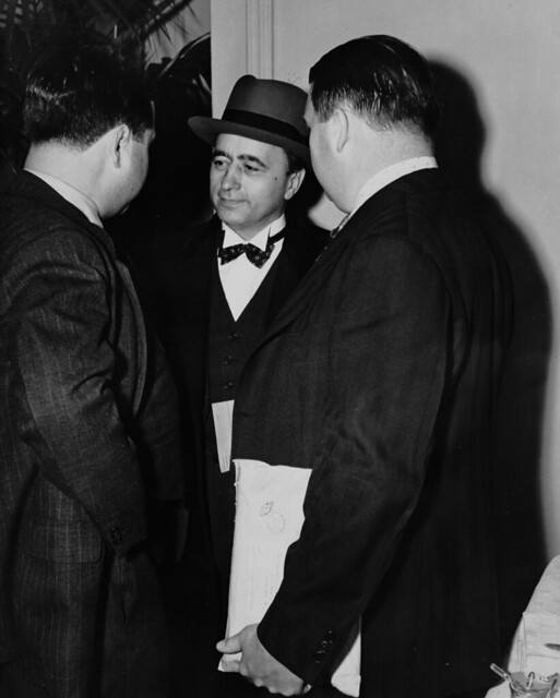 Matthew Woll of the Photo Engravers Union, AFL, in center, talking to Mr. Pearl, publicity director for the AFL, and a newspaper reporter after a five-hour conference with the CIO at the Hotel Biltmore, March 10, 1939
