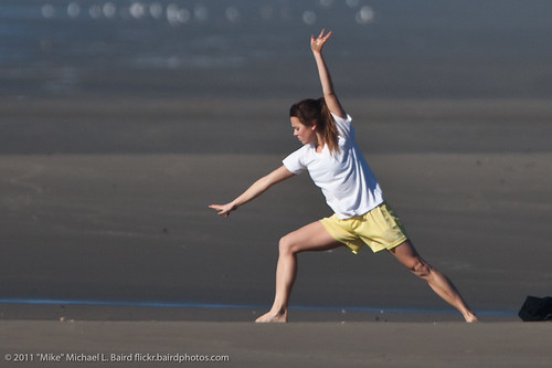 A woman exercising on the beach.