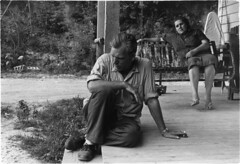 Man sitting on porch steps, smoking cigarette; woman on porch swing, Eastern Kentucky, 1964, by William Gedney