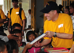SIHANOUKVILLE, Cambodia (March 2, 2011) Avaiton Support Equipment Technician 1st Class Philip A. Lapan, assigned to the forward-deployed amphibious assault ship USS Essex (LHD 2), hands out books during a community service project at the Village d'enfant de Sihanoukville orphanage. (U.S. Navy photo by Mass Communication Specialist 2nd Class Casey H. Kyhl)