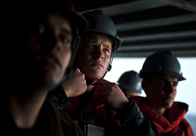 Sailor fastens chin strap during man overboard drill.