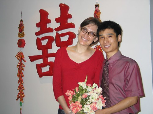 John and I holding a bouquet of flowers after our marriage registration