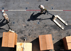 PACIFIC OCEAN (March 29, 2011) Marines position humanitarian assistance and disaster relief supplies on the flight deck of the forward-deployed amphibious assault ship USS Essex (LHD 2). Essex, with the embarked 31st Marine Expeditionary Unit, is currently operating off the coast of Kesennuma in northeastern Japan in support of Operation Tomodachi. (U.S. Navy photo by Mass Communication Specialist 2nd Class Casey H. Kyhl)