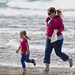 Mother and daughter scamper across the wet sand and breaking waves