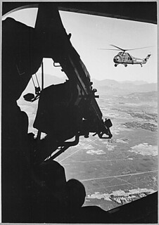 Vietnam: helicopter and soldier approaching target. Viet Nam Photo Service., ca. 1965