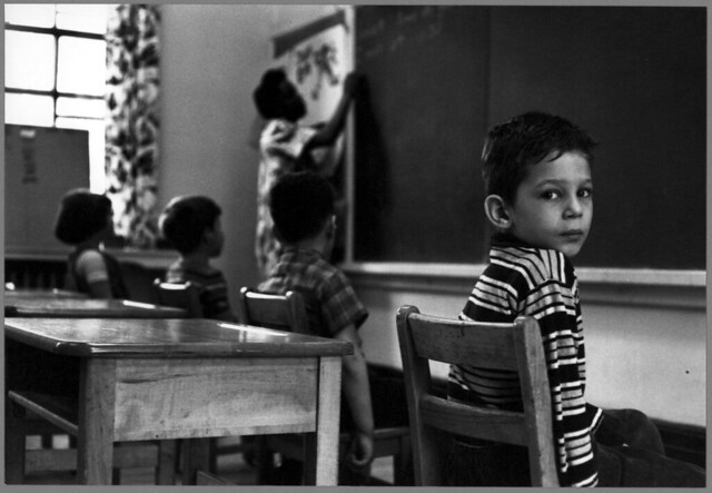 Teacher at chalkboard with three students watching, one student turned to face the camera, St. Joseph's School for the Deaf, by William Gedney c.1960