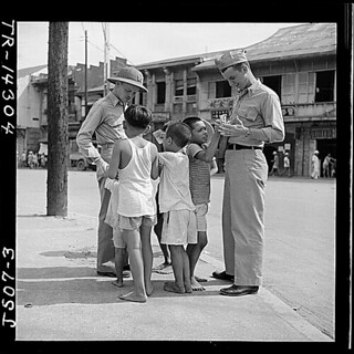 Filipino children make friends with two Naval officers in downtown Manila, hoping for a gift in return., 05/1945