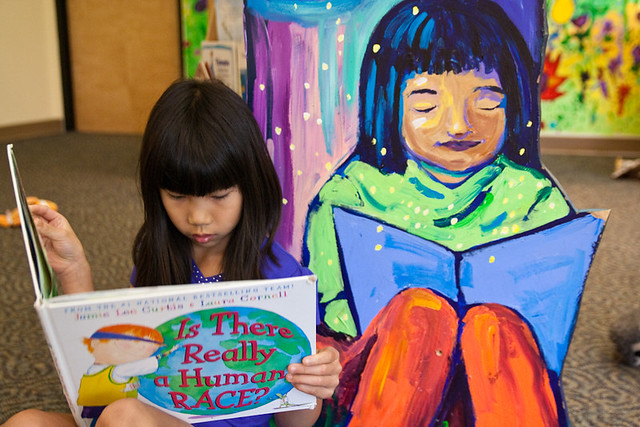 Asian Girl Reading a Book next to Painting of Girl Reading Book Grand Rapids Children's Museum June 11, 20119