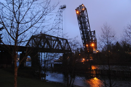 Open train bridge, tower, Hiram's Locks, overcast, trees, water, lights, Seattle, Washington, USA by Wonderlane
