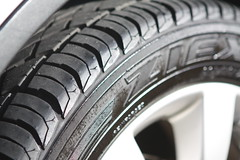 bumper(0.0), tire(1.0), automotive tire(1.0), automotive exterior(1.0), wheel(1.0), synthetic rubber(1.0), tread(1.0), rim(1.0), alloy wheel(1.0), black-and-white(1.0), spoke(1.0),