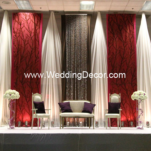 A fuchsia brown ivory wedding backdrop with loveseat and floral stage