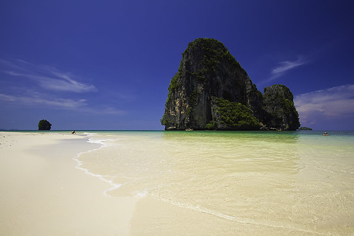a glorious white sand beach, light green sea, with a limestone island in the centre of the frame