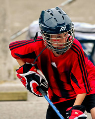 american football(0.0), football--equipment and supplies(0.0), lacrosse(0.0), ice hockey(0.0), goaltender mask(0.0), goaltender(0.0), ice hockey position(0.0), catcher(0.0), baseball positions(0.0), stick and ball games(1.0), hockey protective equipment(1.0), clothing(1.0), sports(1.0), red(1.0), team sport(1.0), hockey(1.0), player(1.0), ball game(1.0), athlete(1.0),