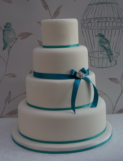 Simple 4 tier wedding cake with thin satin ribbons finished with a vintage