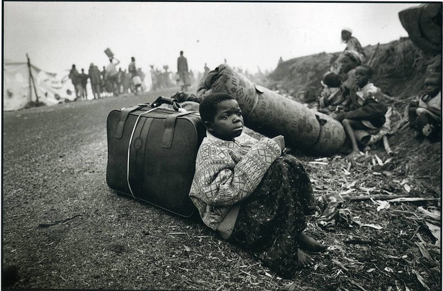 A young Rwandan girl wrapped in adults' clothing sits among her family's few possessions on the road to Goma, Zaire, by David Turnley
