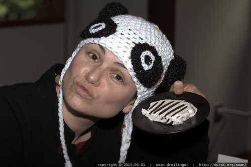 modeling her panda hat with matching black and white birthday cake