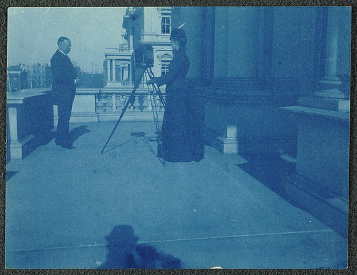[Frances Benjamin Johnston on a balcony of the State, War and Navy Building with a tripod-mounted camera, photographing an unidentified man] (LOC)