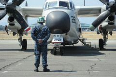 NAVAL AIR FACILITY ATSUGI, Japan (March 29, 2011) A crew captain with Providers of Fleet Logistics Support Squadron 30 (VRC-30) waits patiently to signal to the pilot notifying him of the activities taking place around the twin engine cargo aircraft (C-2) before taking off for a training mission. (U.S. Navy photo by Mass Communication Specialist Seaman Apprentice Vivian Blakely)