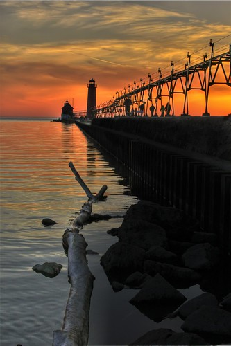 longexposure sunset sun lighthouse sol colors yellow pier rocks michigan grandhaven