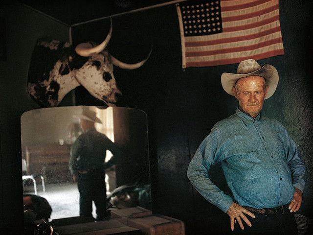 Henry Gray, 72 yr old Arizona rancher - govt wanted his cattle off the land, pausing, lost in his thoughts, behind him a 48-star flag, by William Albert Allard 1970