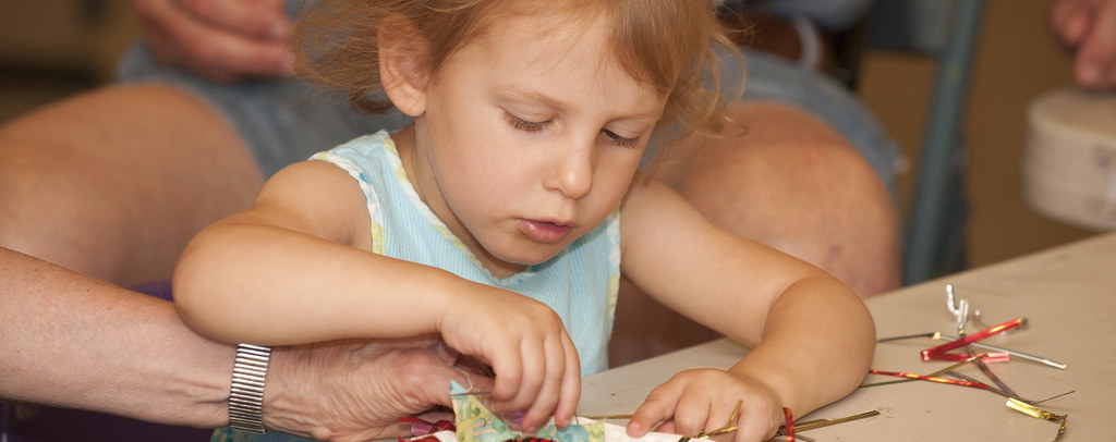 Little girl gluing fabric on a plate.