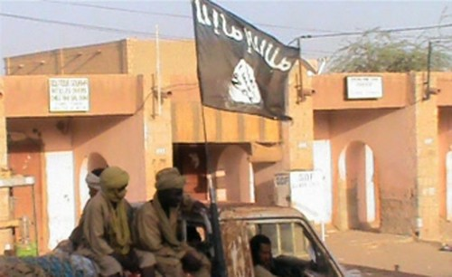 Photograph of a truck carrying members of the Islamist Ansar Dine of northern Mali. There is a black flag symbolizing there Islamic orientation flying overhead on the vehicle. by Pan-African News Wire File Photos