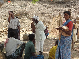 Villagers gathered at their site of worship, interacting with a Myrada official