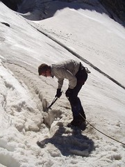 Mike Digging a flat area to sleep for the night at the top of the Glacier Image