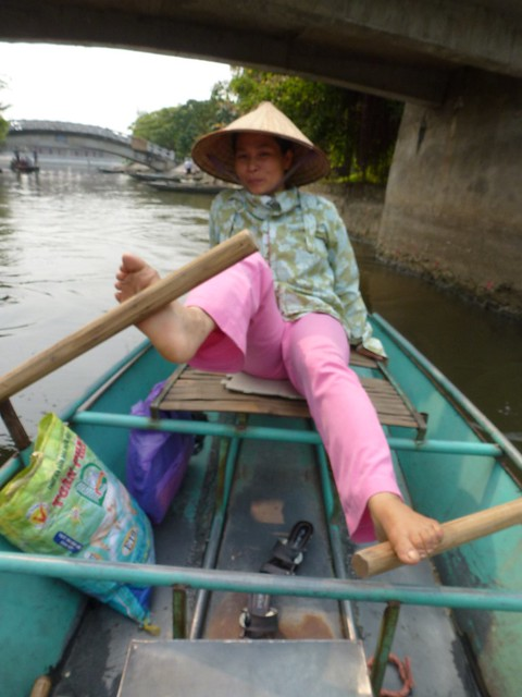 Lady rowing our boat with her feet at Tam Coc