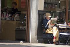 Man leest de krant bij café