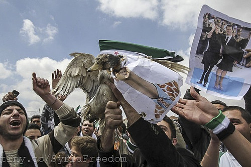 Anti-Assad protesters hold a real duck with its head thrust through a poster of Bashar Assad.
