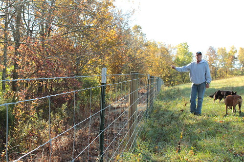 Larry Woods with the fencing installed through the EQIP program. Now the cattle are kept out of the wooded valleys.