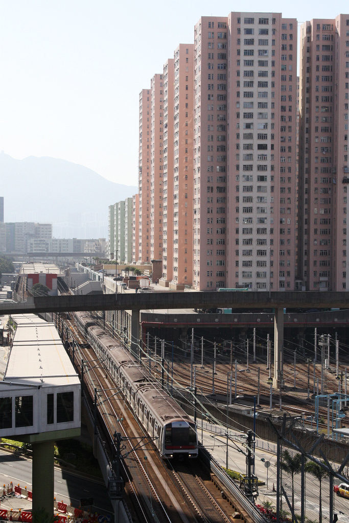 MTR train departs Kowloon Bay station: Kowloon Bay depot is located alongside, underneath the Telford Garden housing estate