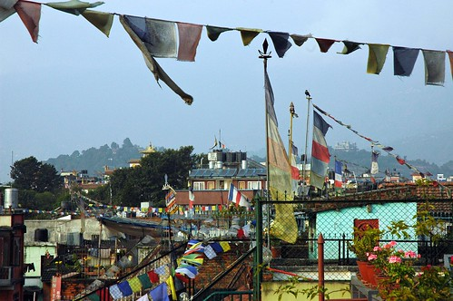 Among Tibetan Buddhist prayer flags, Kopan Monastery as seen from Boudha, Kathmandu, Nepal