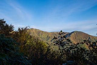 左側の木々から朝日岳と五輪山を展望