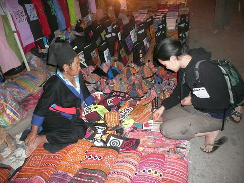 A fabric vendor and traveler at a market in Luang Prabang, Laos.