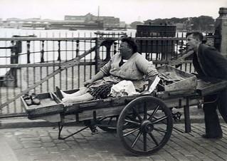 Vrouw wordt vervoerd op handkar / Woman transported on a handcart
