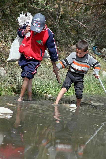 タシュクルガン、湿地帯を歩く少年たち