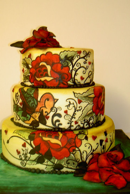 An Alternative Wedding Cake with an all over painted design and 2 large red