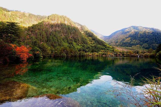 海子的四周是茂密的树林,湖水掩映在重重的翠绿之中,像是一块晶莹剔透