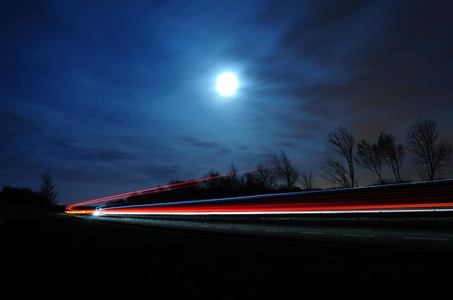 Light trails of two passing lorries with the moon