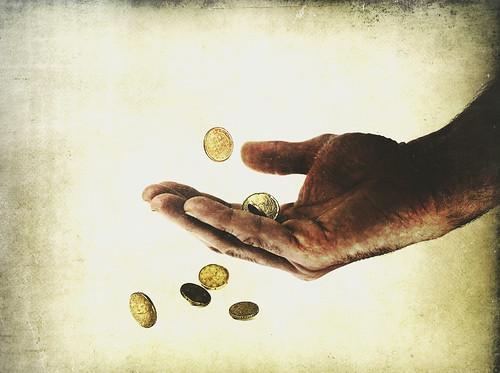 Ilustración: unas monedas se escapan entre los dedos de una mano