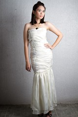 sleeve(0.0), cocktail dress(0.0), bridesmaid(0.0), prom(0.0), bridal party dress(1.0), bridal clothing(1.0), neck(1.0), textile(1.0), gown(1.0), clothing(1.0), abdomen(1.0), woman(1.0), female(1.0), satin(1.0), formal wear(1.0), photo shoot(1.0), human body(1.0), wedding dress(1.0), dress(1.0),