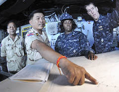 GULF OF THAILAND (Feb. 27, 2011) Royal Cambodian Navy Cmdr. In Sokhemra points out a course on the chart table during a ship tour aboard the forward-deployed amphibious assault ship USS Essex (LHD 2). (U.S. Navy photo by Mass Communication Specialist 2nd Class Greg Johnson)